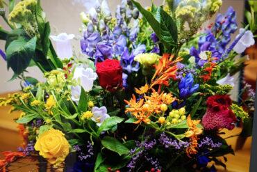 uitvaartzorgnop-megelijkheden-bloemwerk-kleurrijk-groot-op kist